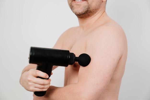 Mann benutzt massagepistole. medizin-sportgerät hilft muskelschmerzen nach dem training zu reduzieren,