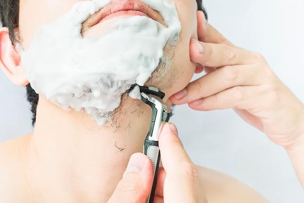 Mann benutzt rasierer