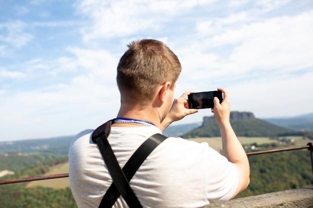 Mann benutzt sein handy im freien und macht ein foto im landschaftspark