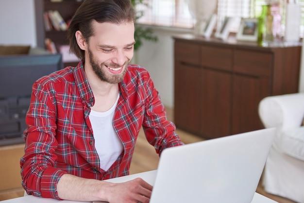 Mann benutzt seinen computer, um mit freunden in kontakt zu treten