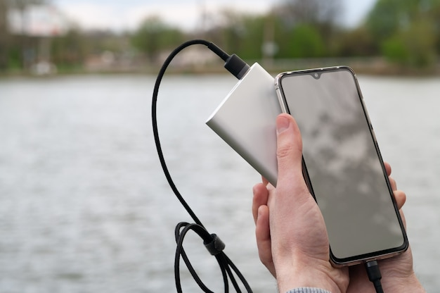 Mann benutzt smartphone mit leerem weißen bildschirm, während er von der powerbank auflädt