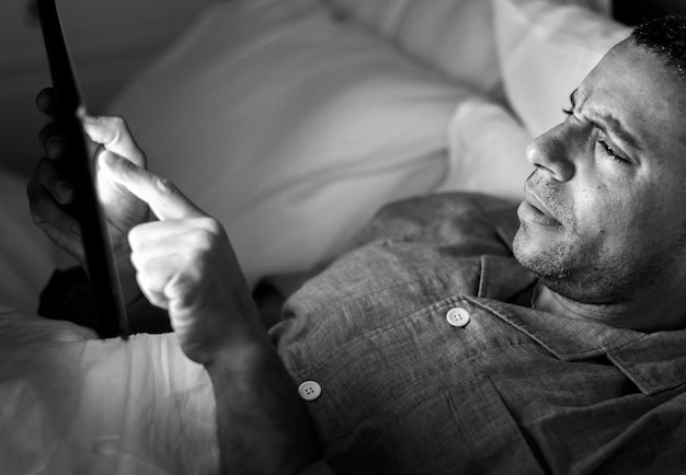 Mann benutzt telefon auf einem bett
