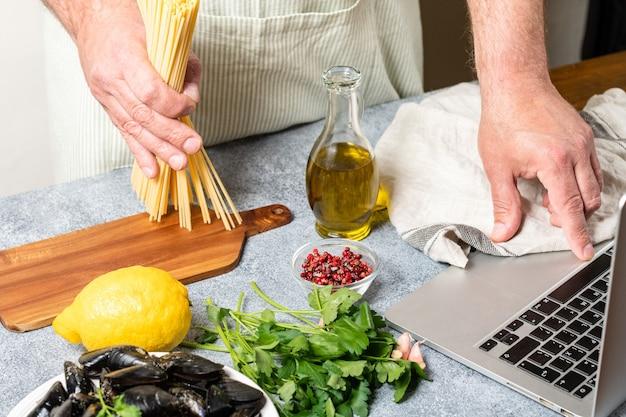 Mann beobachten kulinarische meisterklasse online und lernen, wie man spaghetti mit muscheln von meeresfrüchten kocht