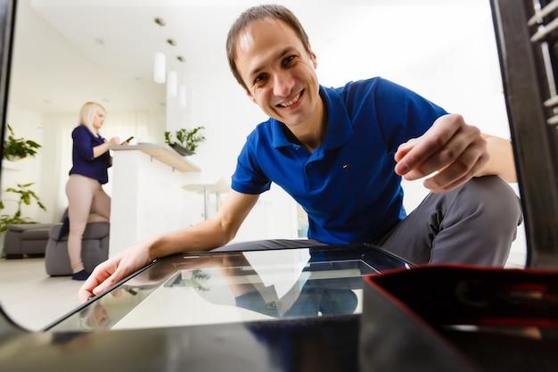 Mann beobachtet etwas im ofen in seiner küche kochen und bückt sich, um in den ofen zu schauen, um zu überprüfen, ob es fertig ist