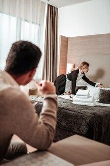 Mann beobachtet. sexy junge blonde haushälterin, die hart arbeitet, während mann sie beobachtet