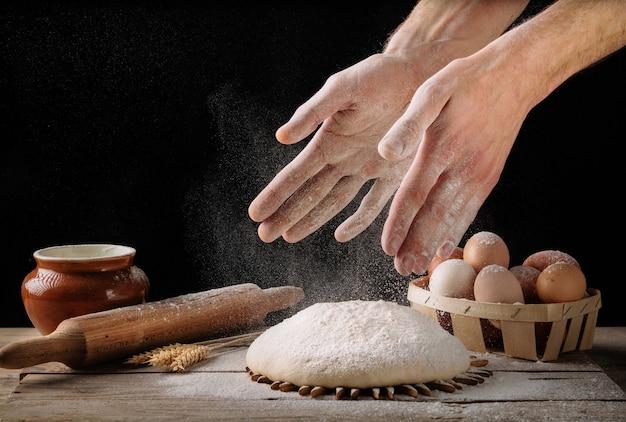 Mann bereitet brotteig auf einem hölzernen küchentisch vor. hausgemachtes brot machen.