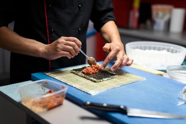 Mann bereitet eine sushi-bestellung zum mitnehmen vor