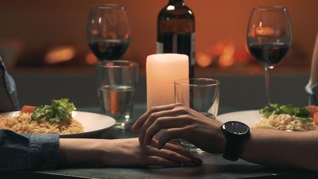 Mann berührt die hand einer frau während eines romantischen dates. nahaufnahme
