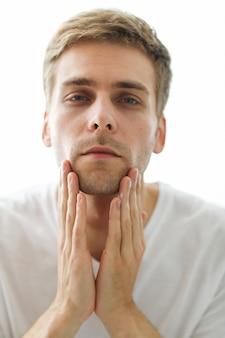 Mann berührt seinen bart, bereit zum rasieren.
