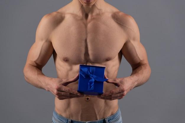 Mann beschnittene ansicht mit passendem torso halten geschenkbox grauer hintergrund, geschenk.