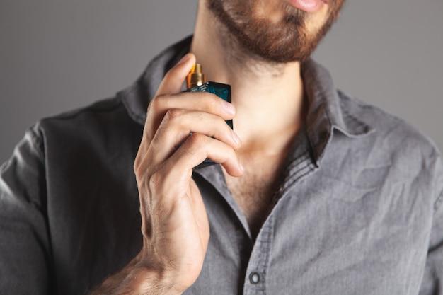 Mann besprüht sich mit parfüm