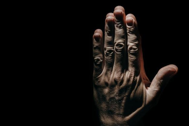 Mann betende hände in der dunkelheit