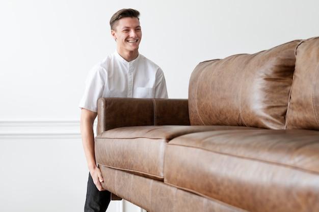 Mann bewegt ein sofa in ein neues zuhause