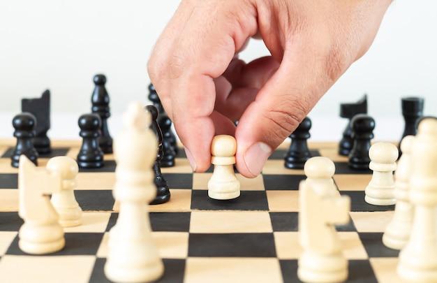 Mann bewegt schachfigur im spiel auf schachbrett