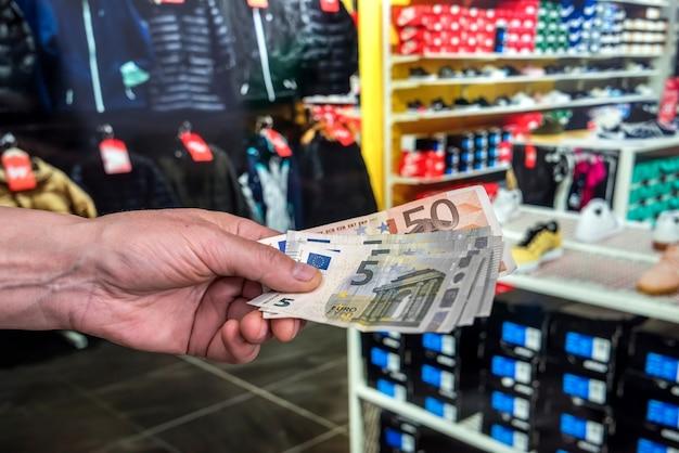 Mann bezahlt für einkäufe in einem bekleidungsgeschäft einkaufen