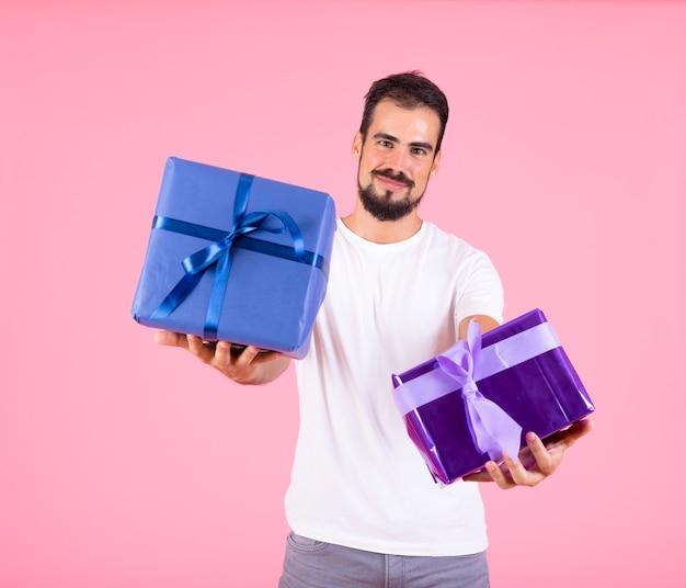 Mann bietet eingewickeltes geschenk über rosa hintergrund an