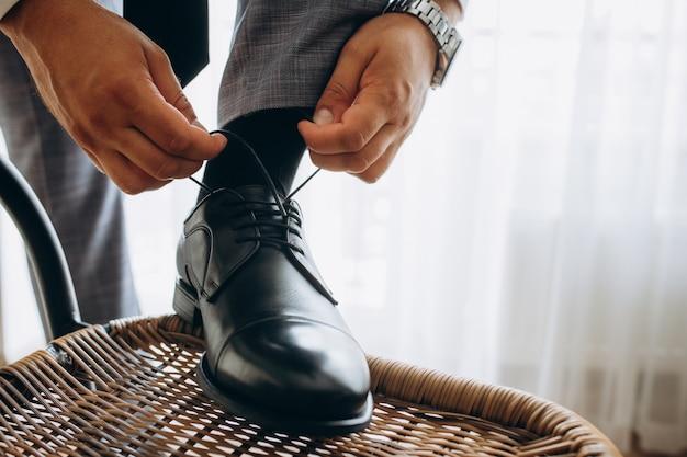 Mann bindet seine glänzenden neuen schwarzen ledergeschäftsschuhe