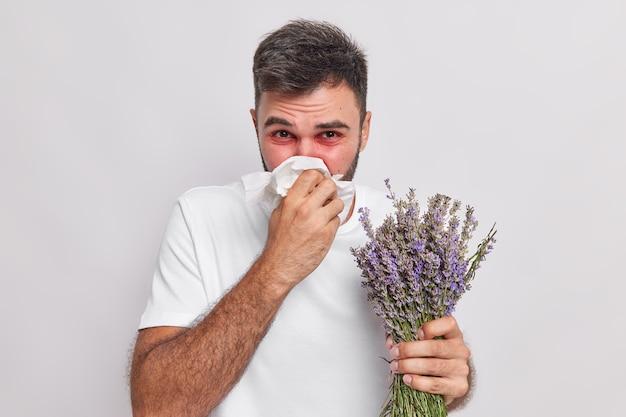 Mann bläst die nase im taschentuch hat niesen und rhinitis-allergie gegen lavendelrot geschwollene augen leidet an unangenehmen symptomen, die auf der weißen wand isoliert sind. krankheitskonzept