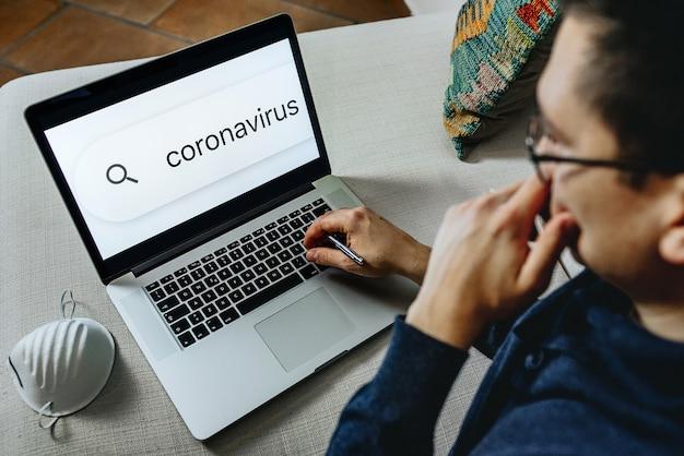 Mann bleiben über coronavirus-nachrichten auf dem laptop zu hause informiert.