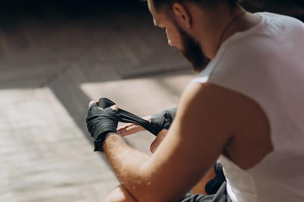 Mann-boxer, der die hände werden fertig zu einem kampf einwickelt. wrapping hands für boxhandschuhe