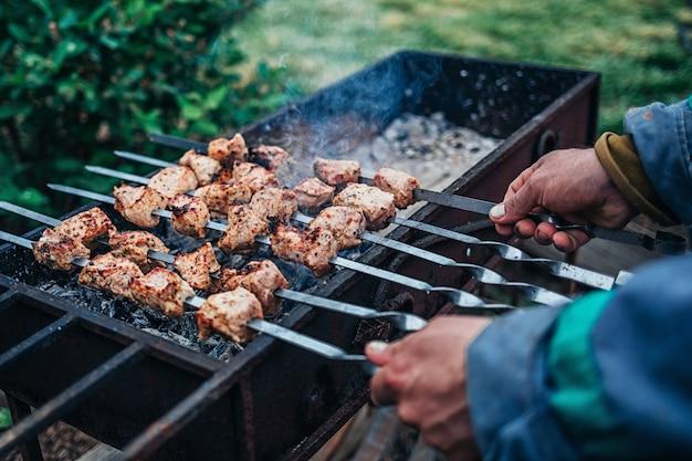 Mann brät kebab auf dem grill