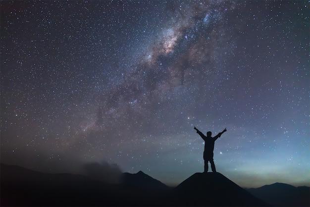 Mann breitet hand auf hügel aus und sieht die milchstraße
