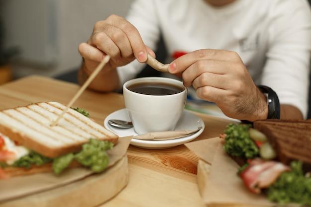 Mann bricht zuckerstange, bevor er sie in kaffeetasse gießt. morgenfrühstück mit frischem kaffee und saftsandwich