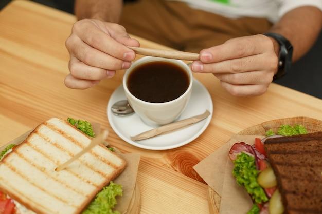 Mann bricht zuckerstange, bevor er sie in kaffeetasse gießt