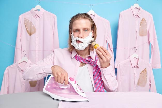 Mann bügelt saubere zerknitterte kleidung auf dem bügelbrett trägt schaumgel auf die wangen auf, um sich in formellem outfit zu rasieren und beschäftigt sich mit täglichen heimroutinen einzeln auf blau