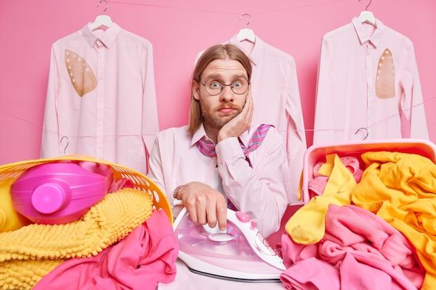 Mann bügelt wäsche hat viel arbeit im haus hat verwirrten gesichtsausdruck trägt runde brille, hemd und krawatte um den hals