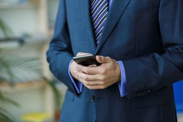 Mann büroangestellter in anzug mit smartphone in der nähe von fenster und palmen