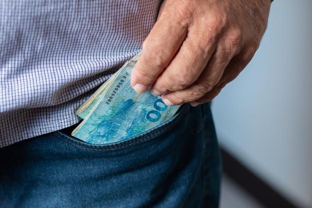 Mann, der 100 brasilianische reais-banknoten aus seiner tasche nimmt.