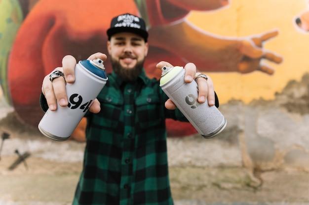 Mann, der aerosoldosen mit den händen hält, die gegen graffitiwand stehen