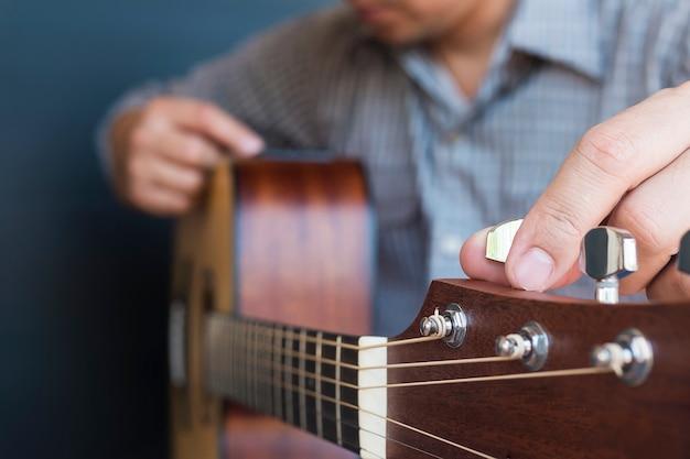 Mann, der akustische gitarre abstimmt