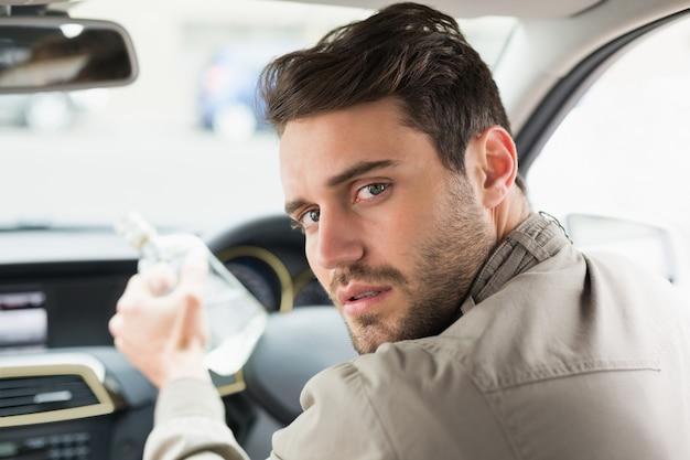 Mann, der alkohol beim fahren trinkt