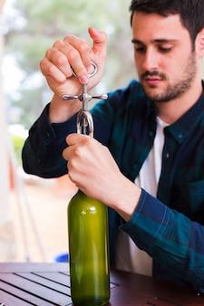 Mann, der alkoholflasche mit öffner öffnet