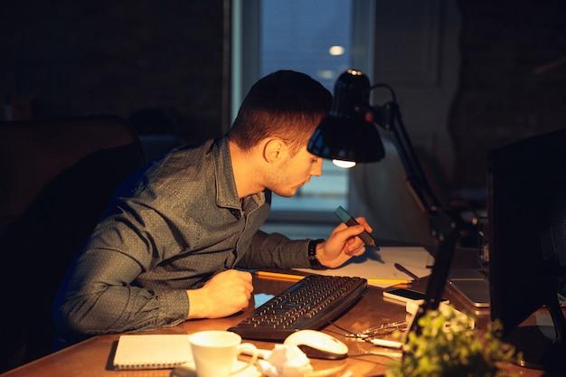 Mann, der allein im büro arbeitet