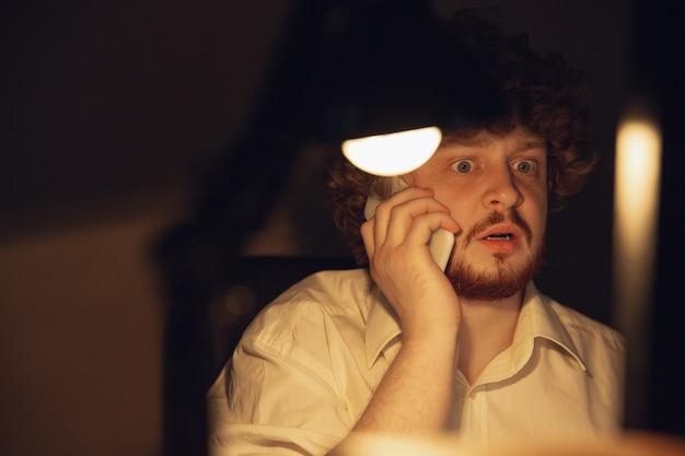 Mann, der allein im büro während des coronavirus oder der covid-19-quarantäne arbeitet und bis spät in die nacht bleibt