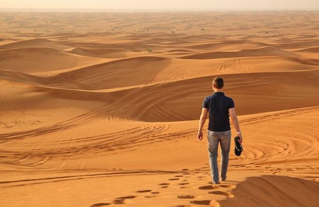 Mann, der alleine in die sonnige wüste nahe bei dubai geht