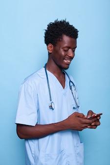 Mann, der als krankenschwester arbeitet und auf smartphone schaut und lächelt