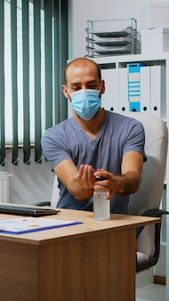 Mann, der am arbeitsplatz eine maske trägt und die hände desinfiziert, bevor er auf der tastatur tippt. unternehmerreinigung mit desinfizierendem alkoholgel gegen corona-virus, arbeiten an einem neuen normalen büroarbeitsplatz im unternehmen