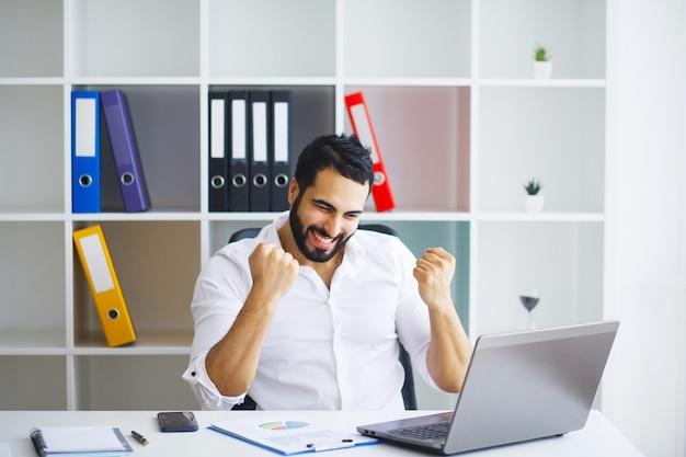 Mann, der am computer im zeitgenössischen büro arbeitet