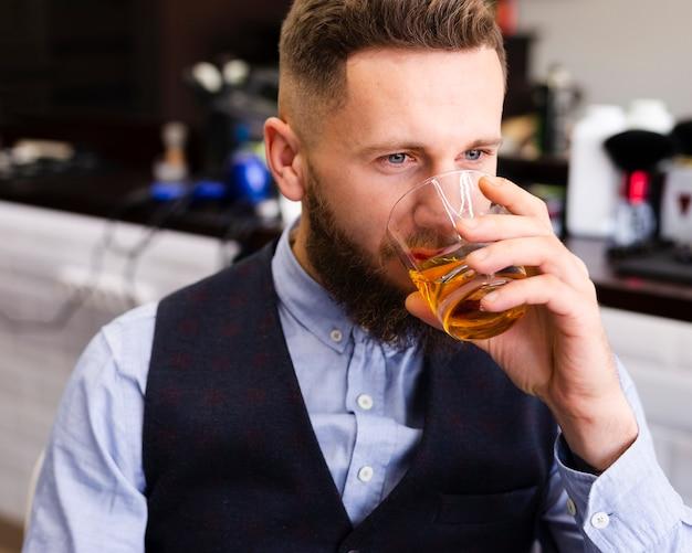 Mann, der am friseursalon trinkt
