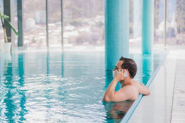 Mann, der am handy im schwimmbad am luxushotel spricht