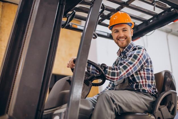Mann, der am lager arbeitet und gabelstapler fährt