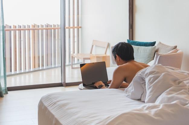 Mann, der am laptop arbeitet, der im urlaub im bett liegt