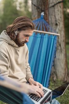 Mann, der am laptop arbeitet, während er in der hängematte sitzt