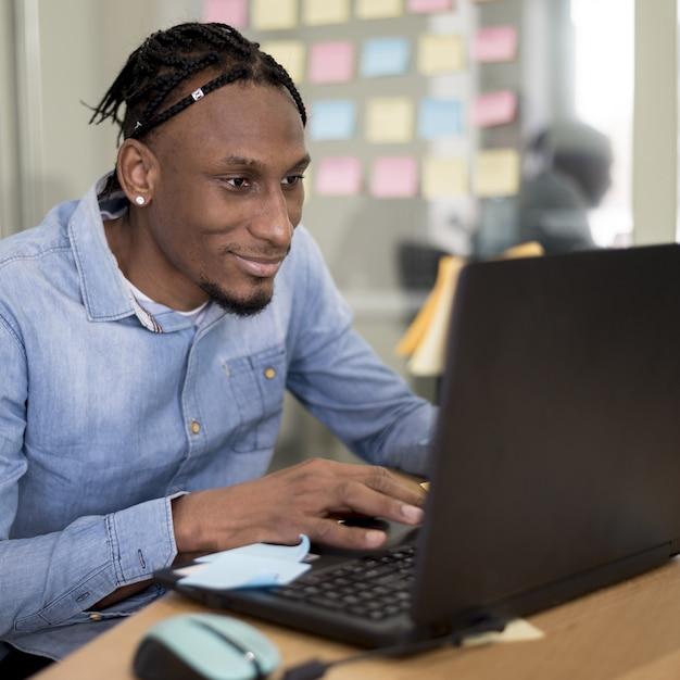 Mann, der am laptop im büro arbeitet