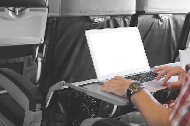 Mann, der am laptop in der flugzeugkabine arbeitet