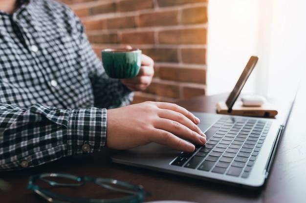 Mann, der am laptop mit einer tasse kaffee zu hause arbeitet.